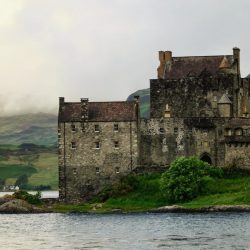 Historic Eilean Donan Castle on grassy shores by the water